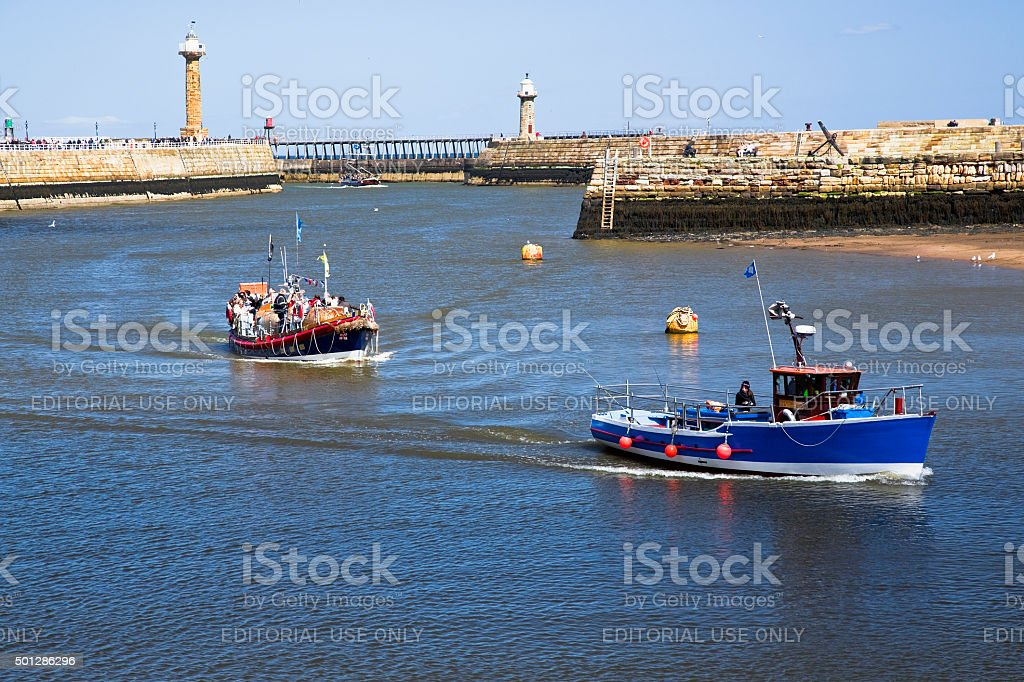 Boats returning to Whitby Harbour royalty-free stock photo