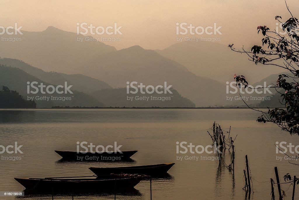 Boats, Rhodedendron and Mountains at Fewa Lake Nepal stock photo