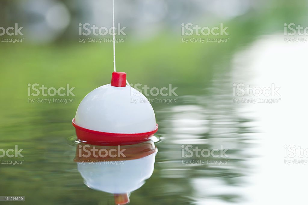 Bobber floating on water with ripples stock photo