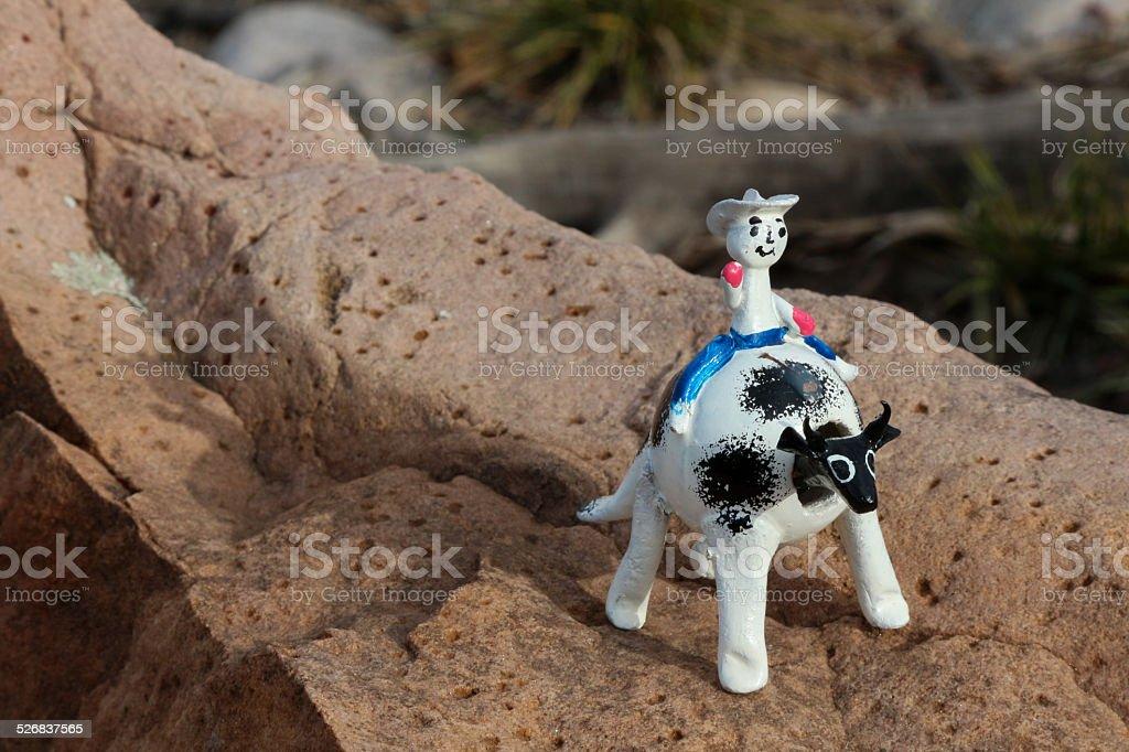 Bobble head cowboy riding a cow on a rock stock photo