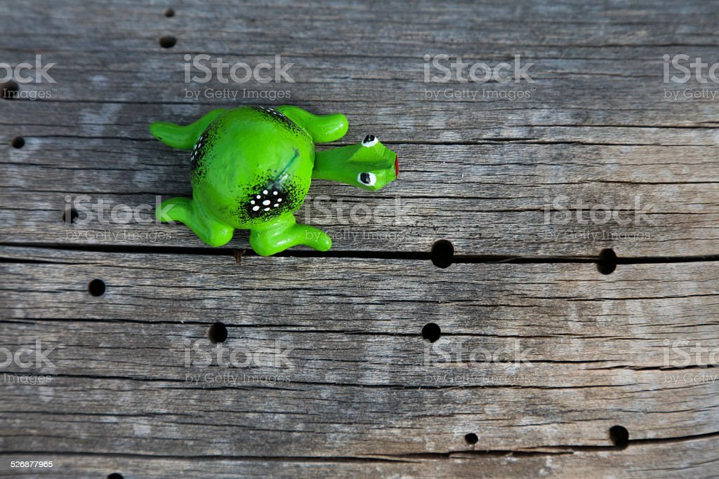 Bobble head frog on wood with holes stock photo
