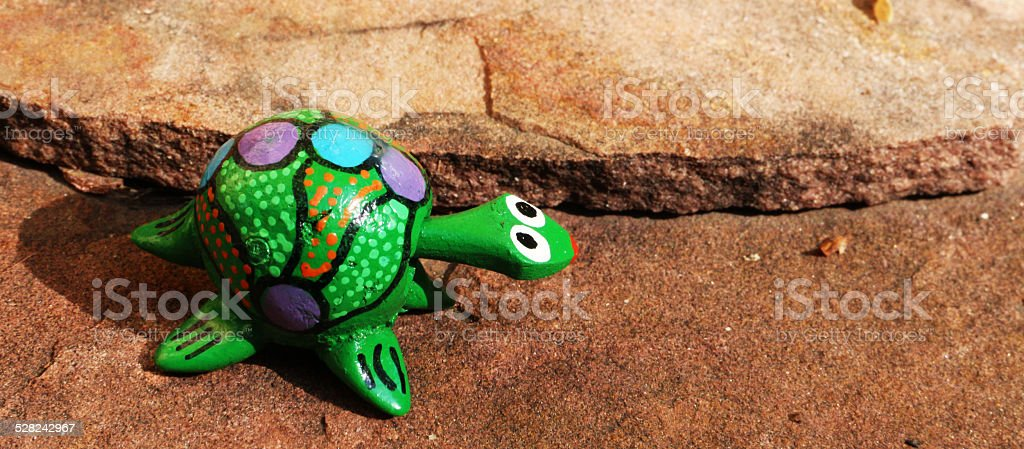 Bobble head green turtle on flagstone looking right stock photo