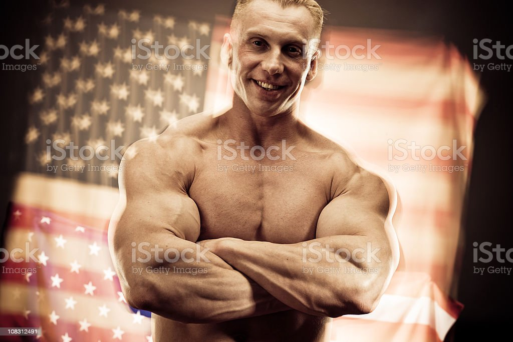 Body Builder posing with American Flag on background royalty-free stock photo