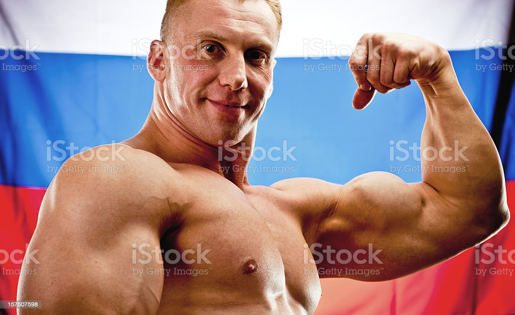 Body Builder Posing with Russian flag on background royalty-free stock photo