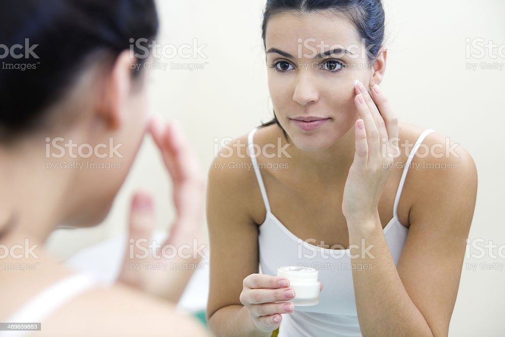 Body care. Woman applying cream on face stock photo
