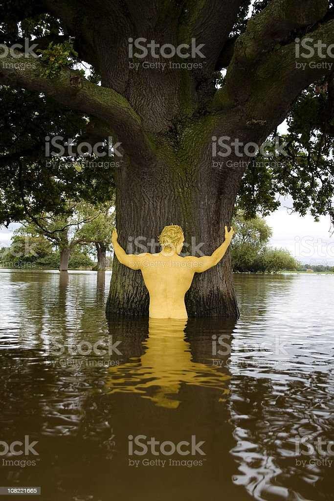 Body Painted Yellow Man Hugging Tree in Flooded Water royalty-free stock photo