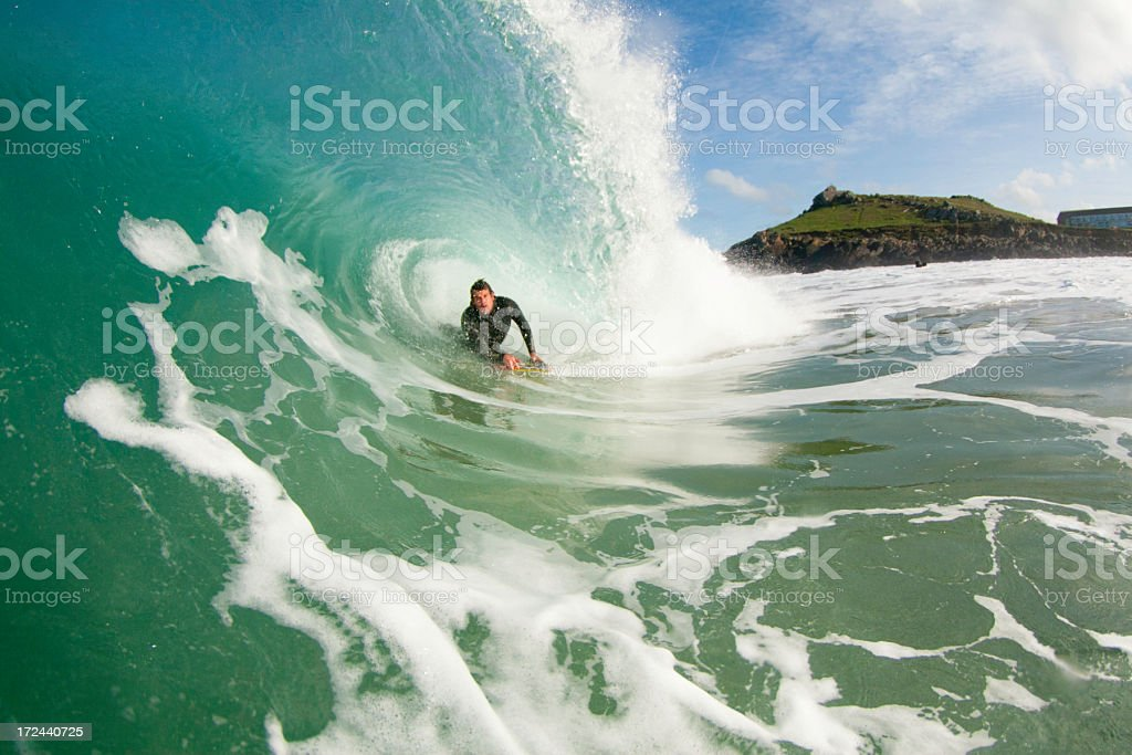 Bodyboarder in the ocean riding a wave stock photo