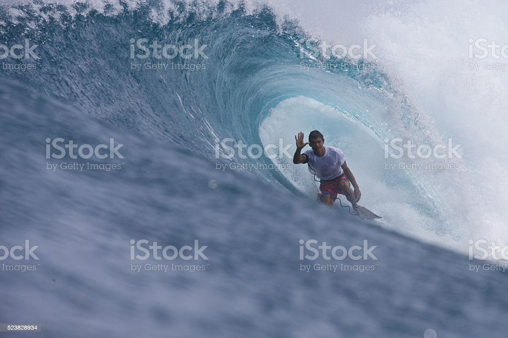 Bodyboarder waves at the camera in a barrel stock photo