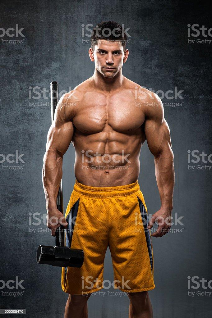 Bodybuilder athlete holding a hammer stock photo