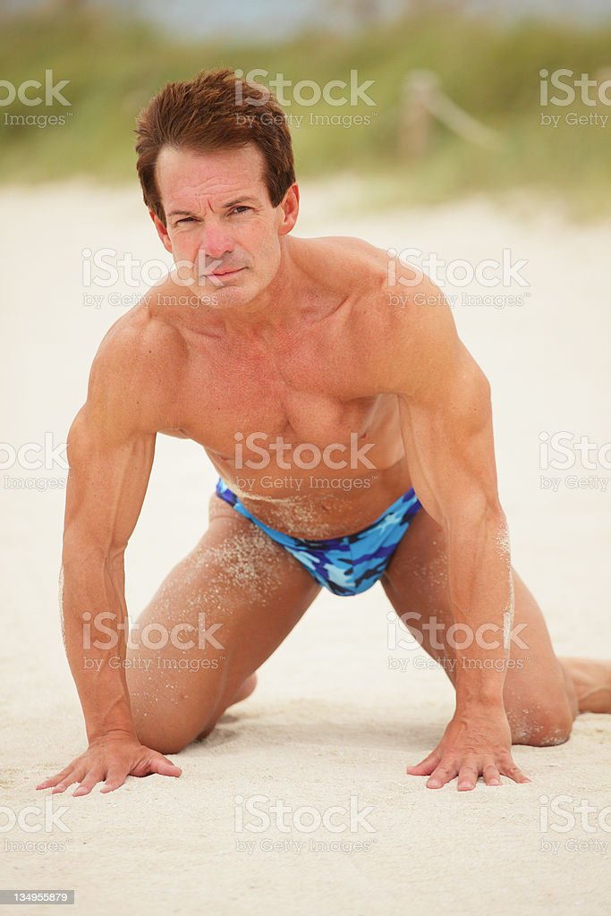 Bodybuilder crawling on the sand stock photo