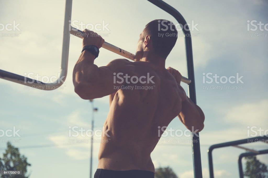Bodybuilder doing pull ups stock photo