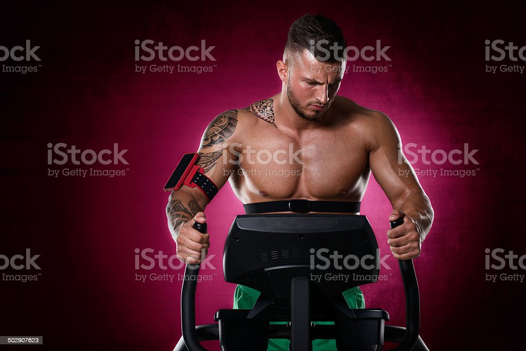 Bodybuilder exercising on stepping machine royalty-free stock photo