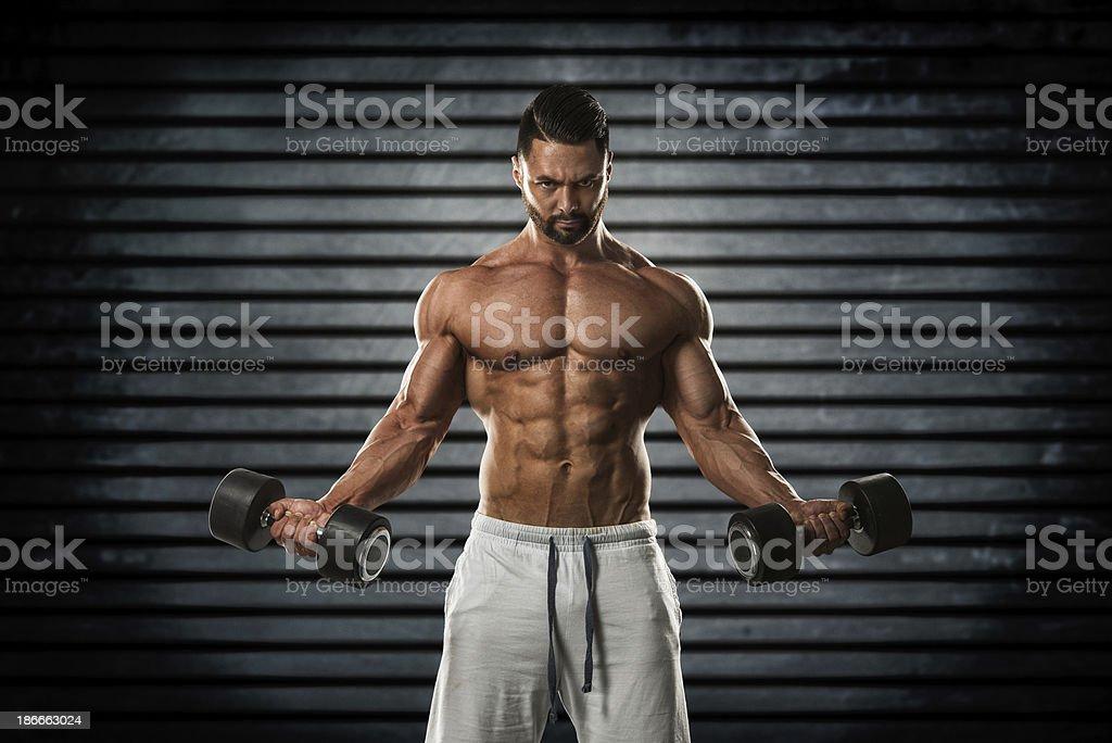 Bodybuilder exercising with dumbbells royalty-free stock photo