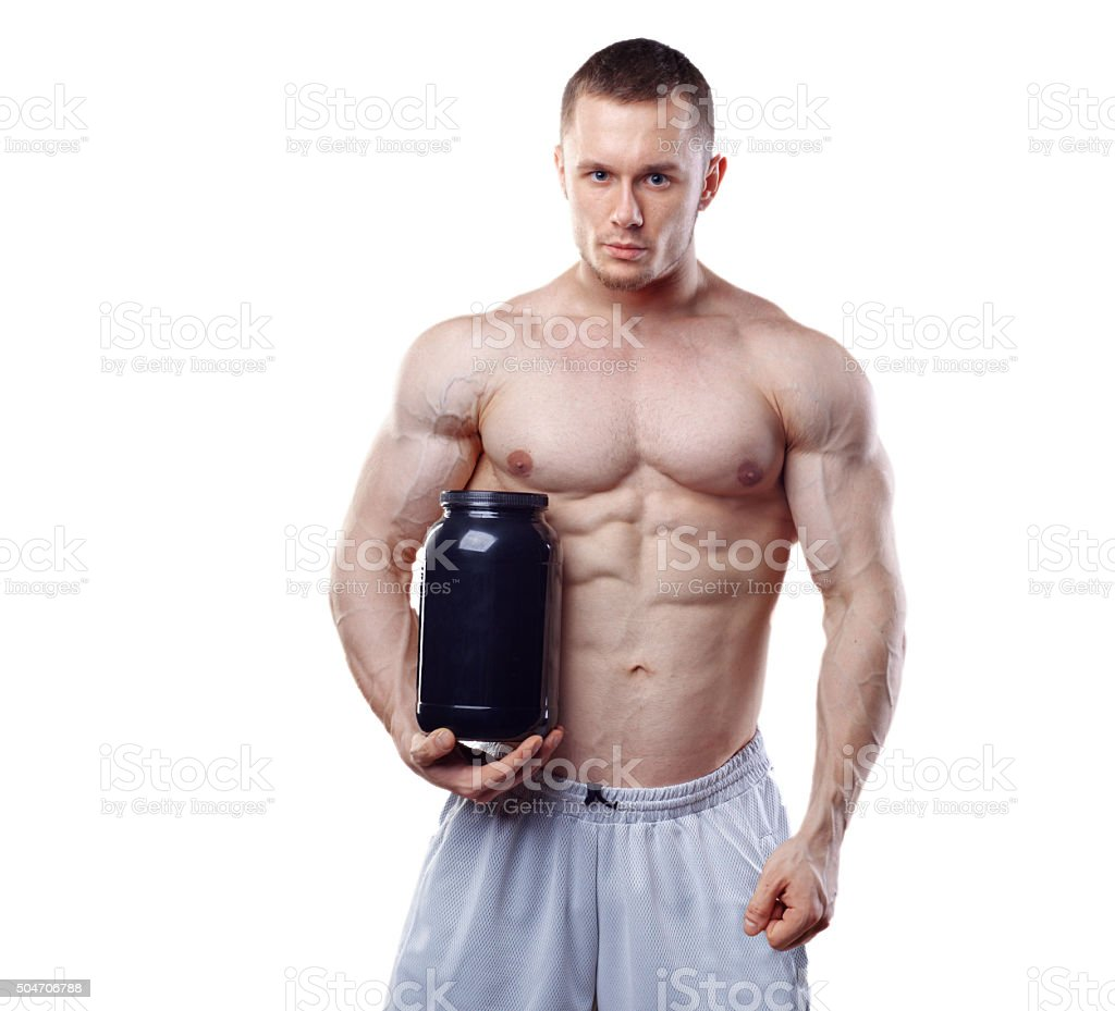Bodybuilder holding a black plastic jar with whey protein isolated stock photo