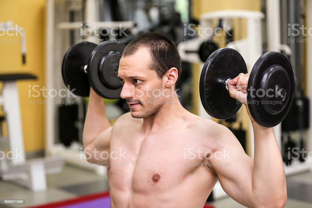 bodybuilder man has two dumbbells in his hands, stock photo