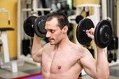 bodybuilder man has two dumbbells in his hands,