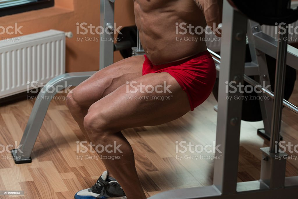 Bodybuilder Performing Barbell Squats Exercise For Legs stock photo