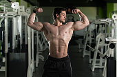 Bodybuilder Performing Front Double Biceps Pose In Gym