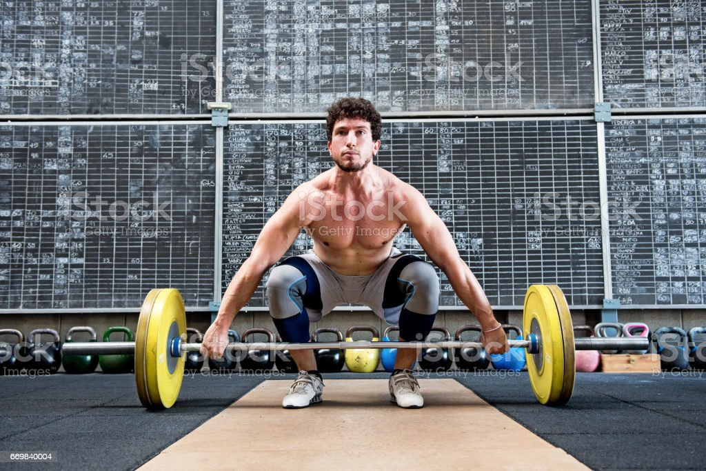 Bodybuilder preparing to lift barbell stock photo