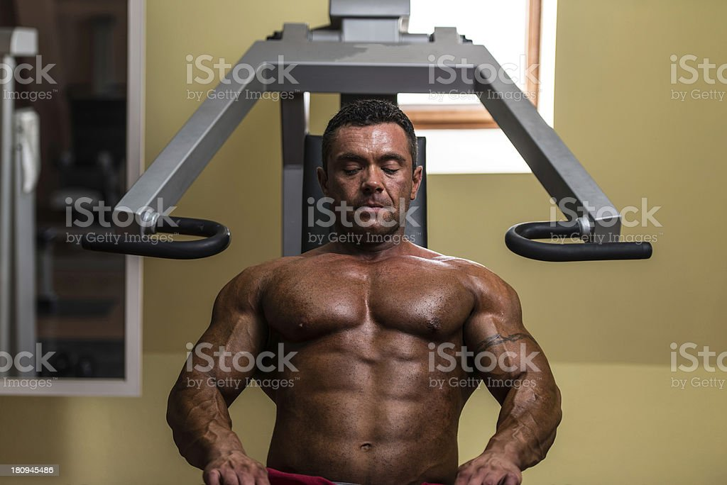 bodybuilder resting after doing heavy weight exercise royalty-free stock photo
