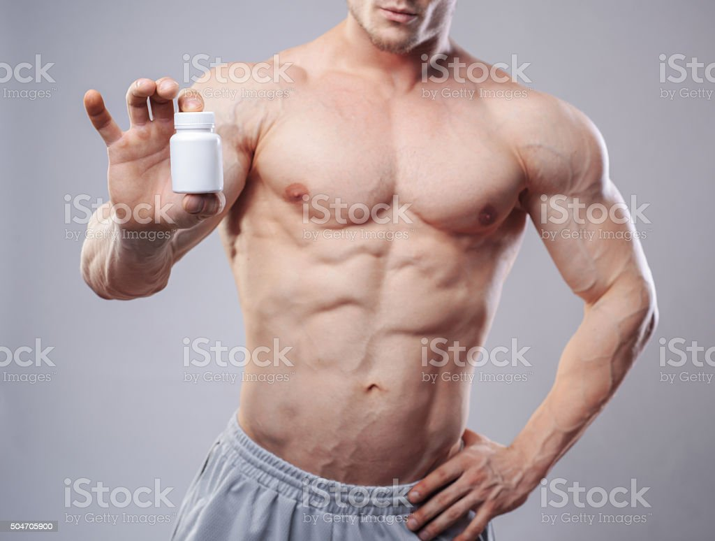 Bodybuilder with a white jar of pills on neitral background stock photo