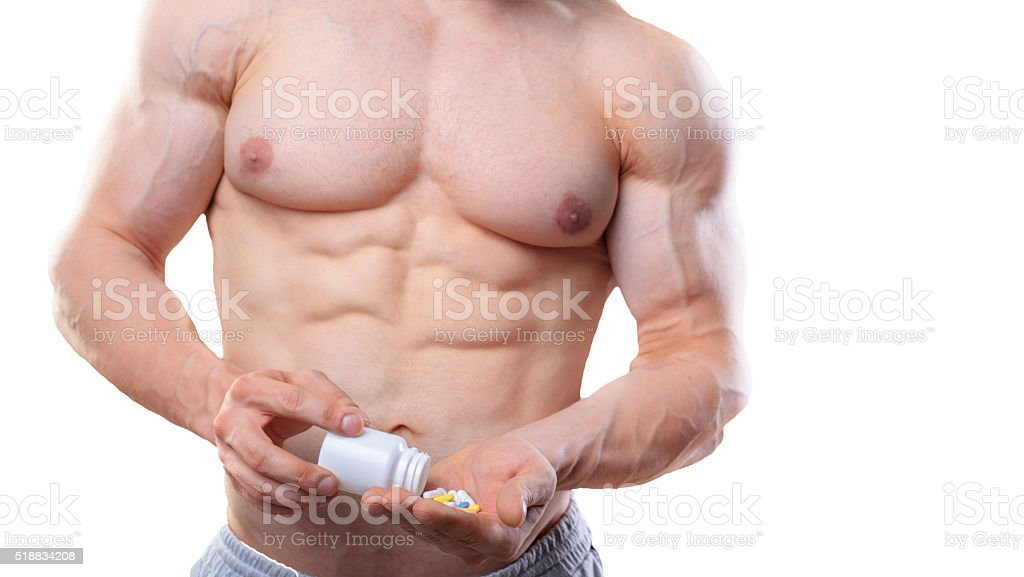 Bodybuilder with jar and pills on isolated white background in stock photo