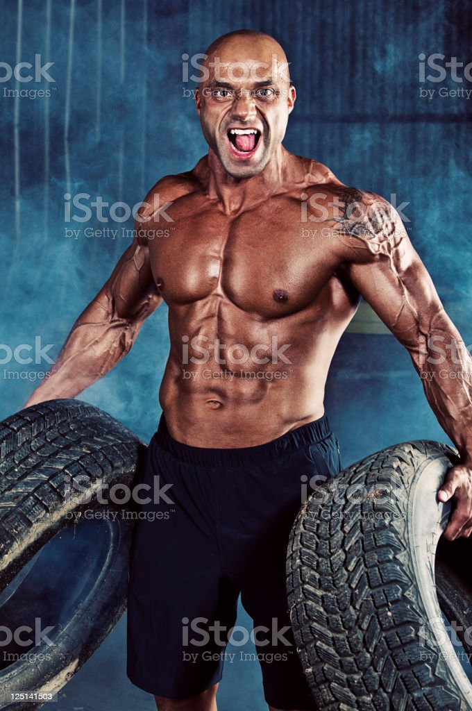 Bodybuilder with tires. royalty-free stock photo