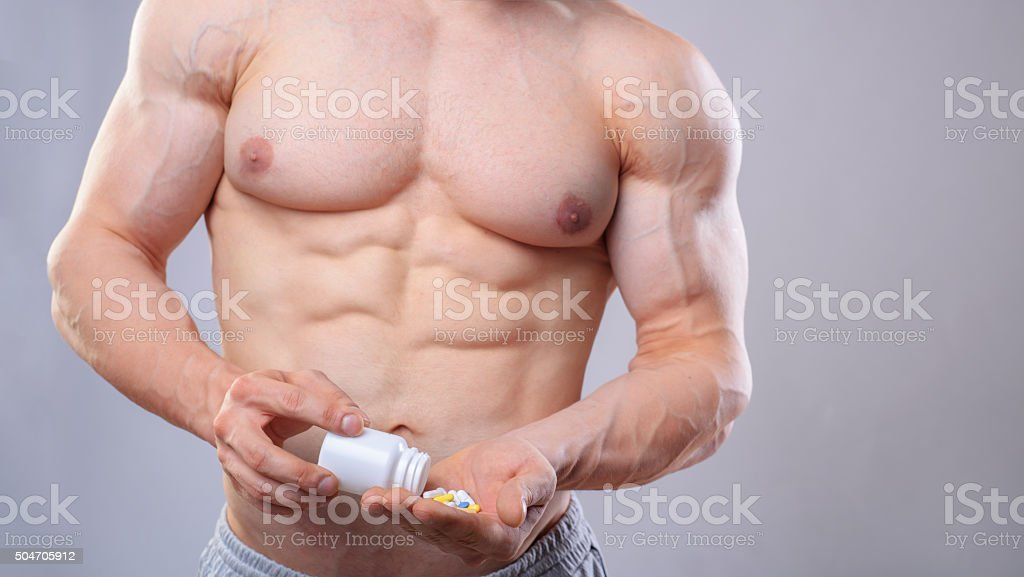 Bodybuilder with white jar and pills on neitral grey background stock photo