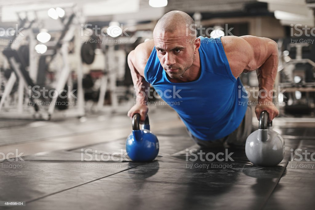 bodybuilder working out and doing push upsat the gym while stock photo