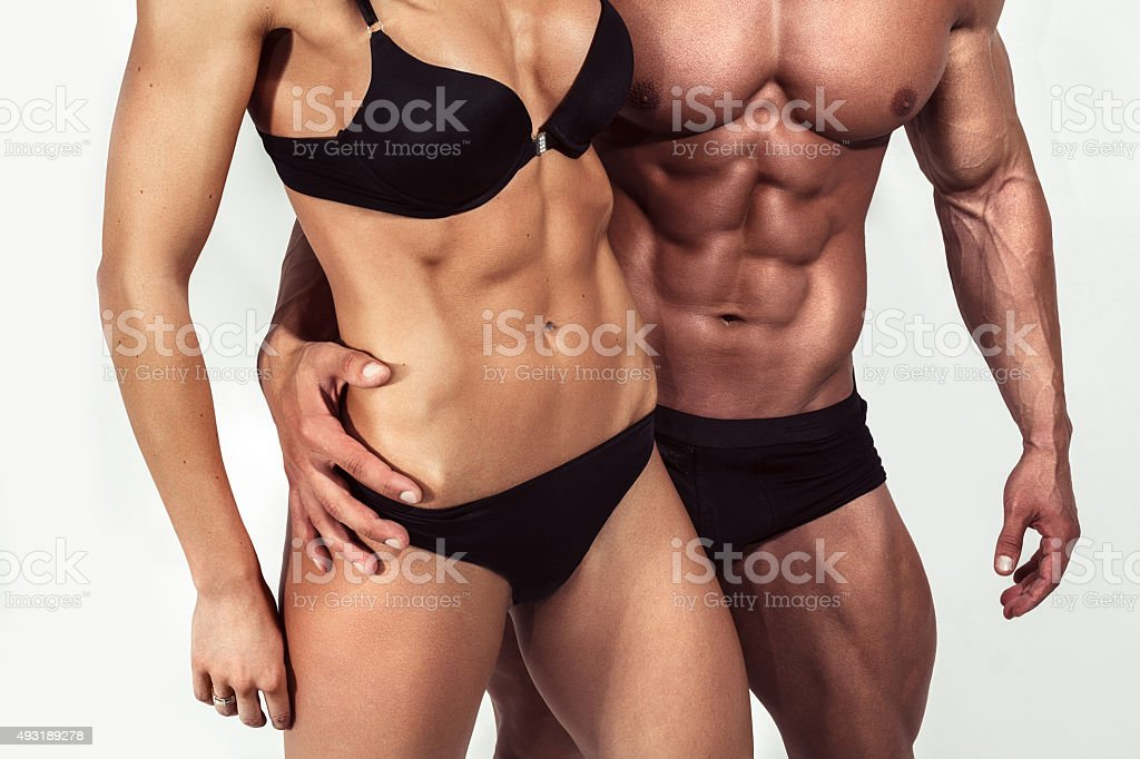Bodybuilding. Strong man and a woman posing on white background stock photo
