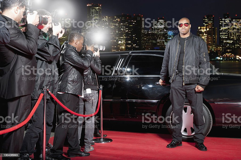 Bodyguard opening limo door on red carpet stock photo