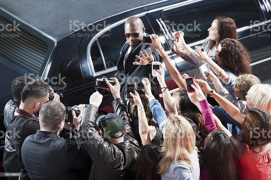 Bodyguard protecting celebrity from paparazzi stock photo