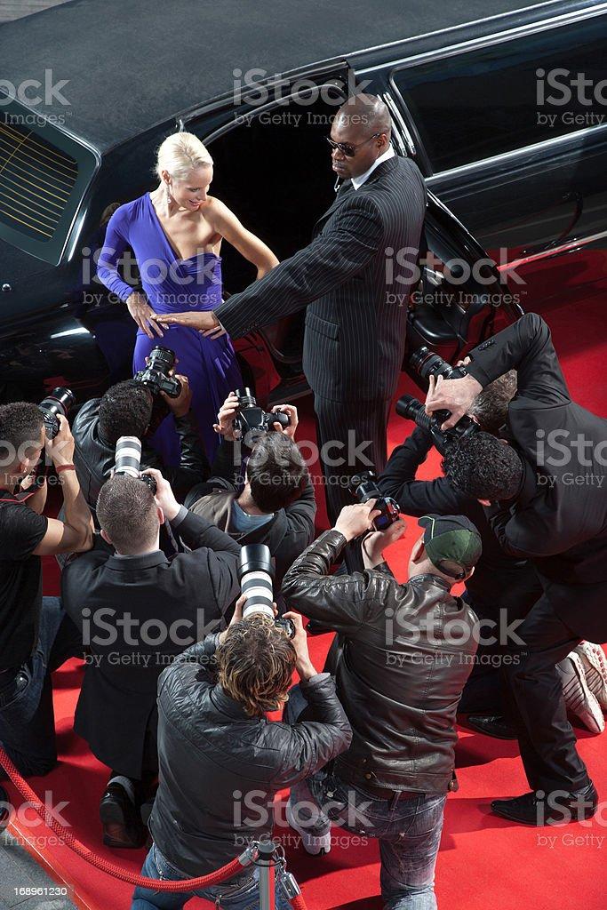 Bodyguard protecting celebrity from paparazzi royalty-free stock photo