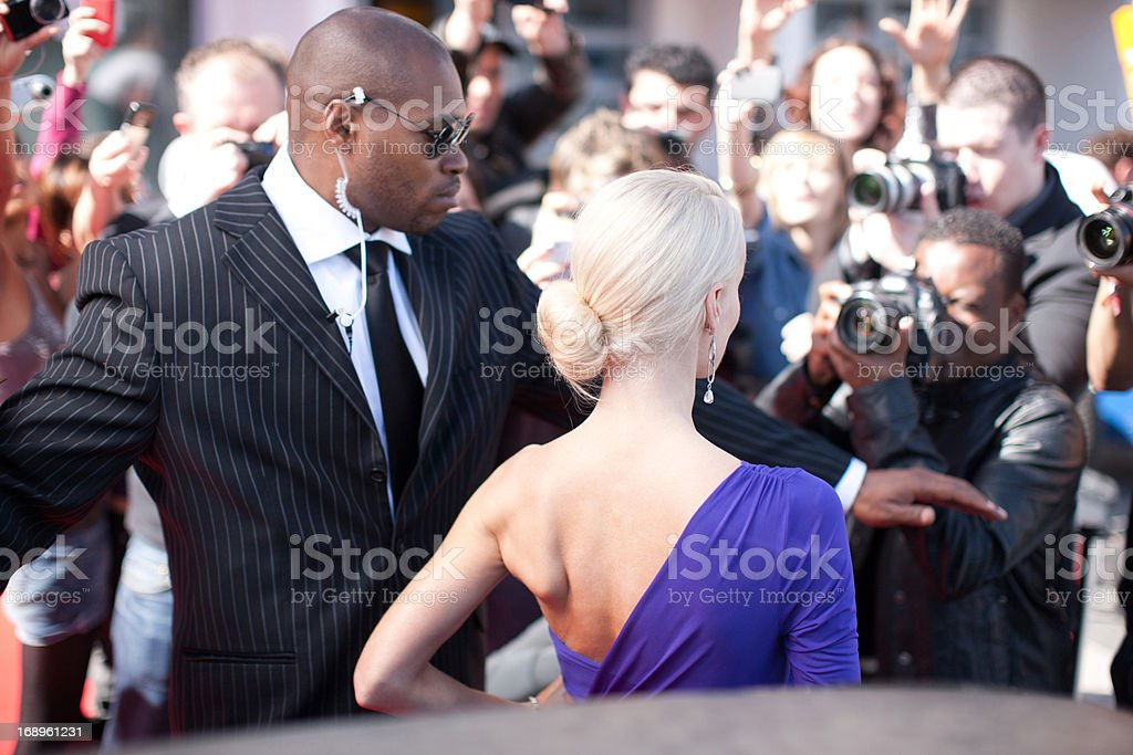 Bodyguard protecting celebrity on red carpet stock photo