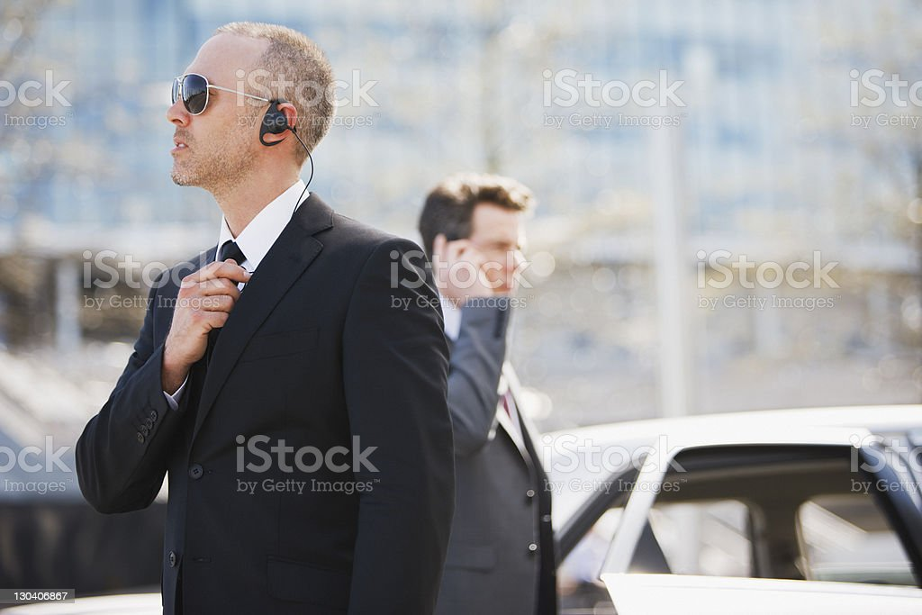 Bodyguard talking into earpiece stock photo