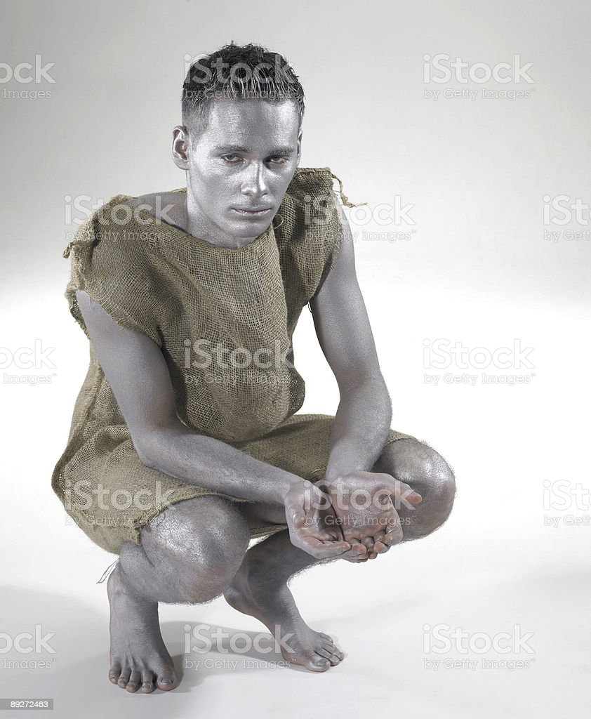 bodypainted poor man cowering on the ground stock photo