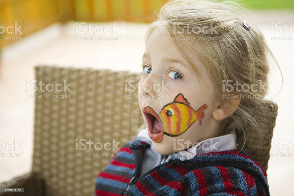 bodypainting - making up fish on girls face stock photo