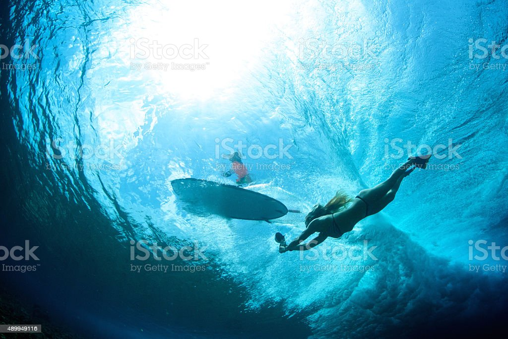 Bodysurfing girl takes a photo of a surfer from underneath stock photo