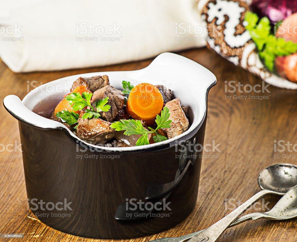 Boeuf bourguignon in  black  pot . Selective focus. stock photo
