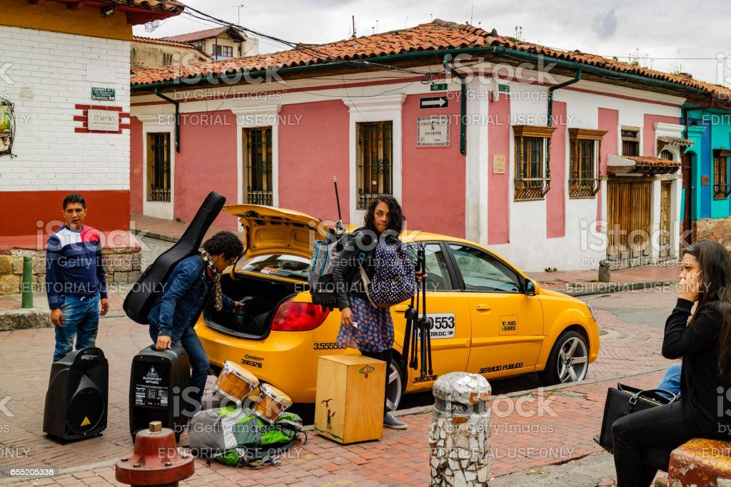 Bogotá, Colombia - A Group of Local Musicians Seen Moving Their Equipment Using a Taxi just of Chorro de Quevedo in the Historic La Candelaria District stock photo
