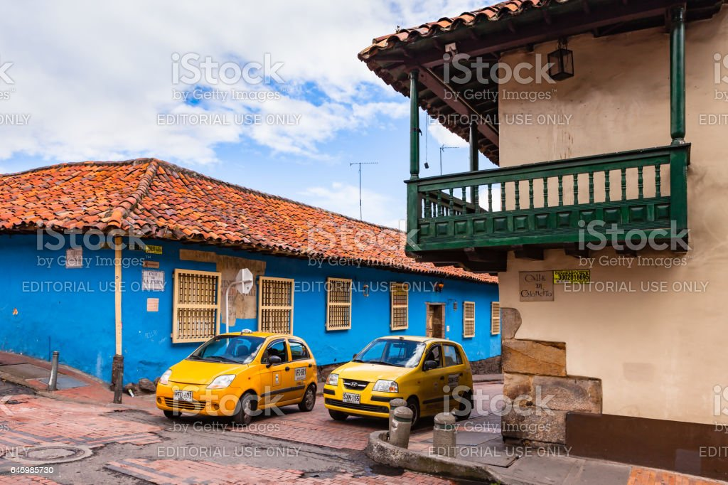 Bogotá Colombia - Two Taxis and Spanish Colonial Architecture, Colourful Walls and Narrow Streets in the Historic La Candelaria District, in the Andean Capital City stock photo