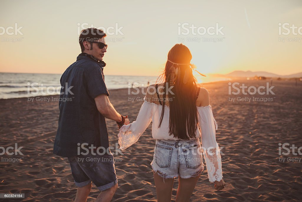 Bohemian couple holding hands on the beach stock photo
