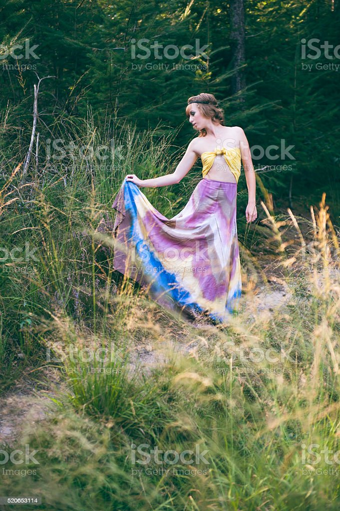 Bohemian girl holding dress stock photo