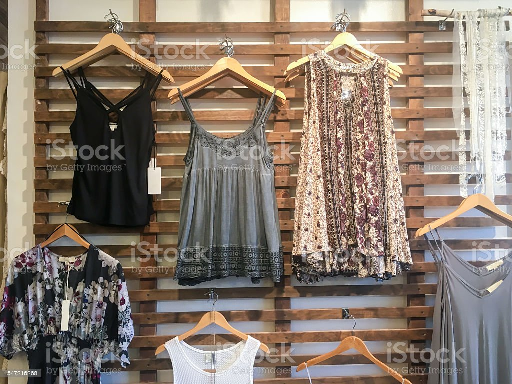 Boho Chic women's clothing hanging on wall stock photo