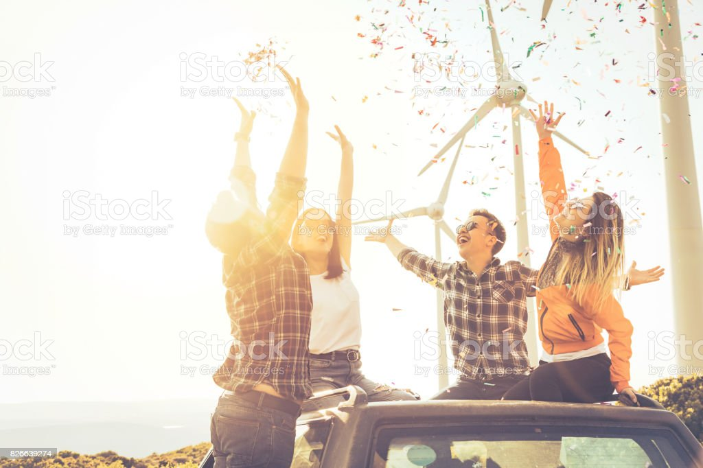 Boho friends enjoying the outdoor party together with confetti in nature stock photo