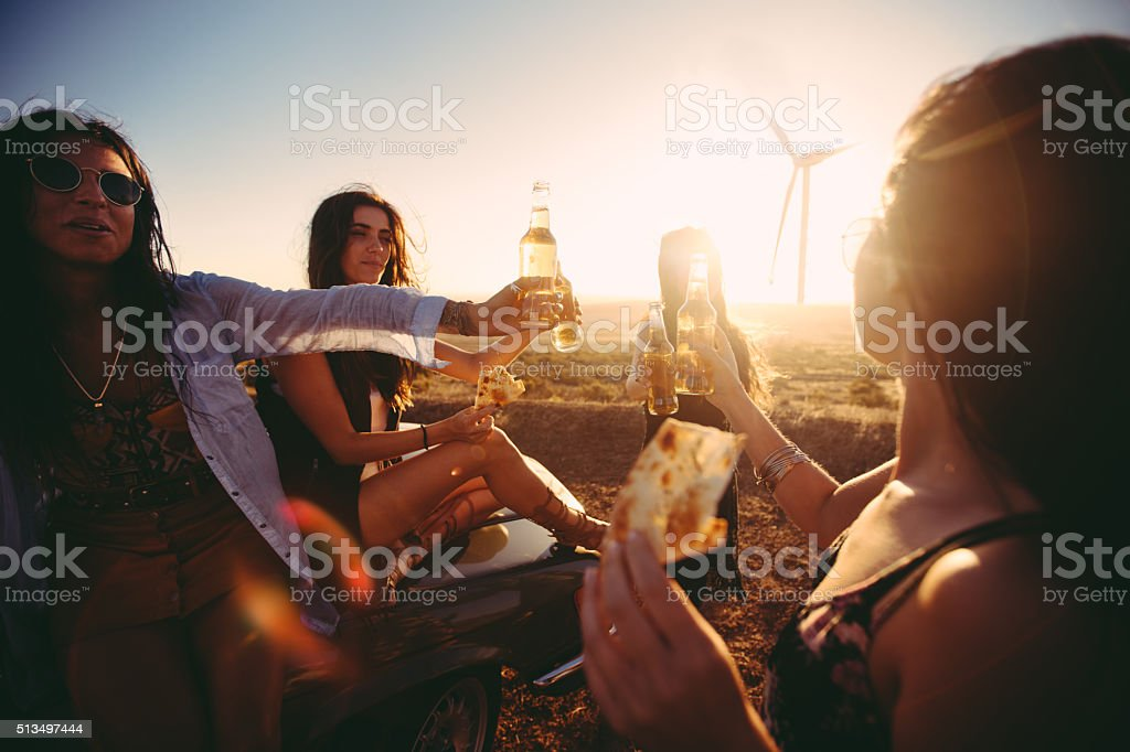 Boho Friends toasting at sunset with beer and pizza stock photo