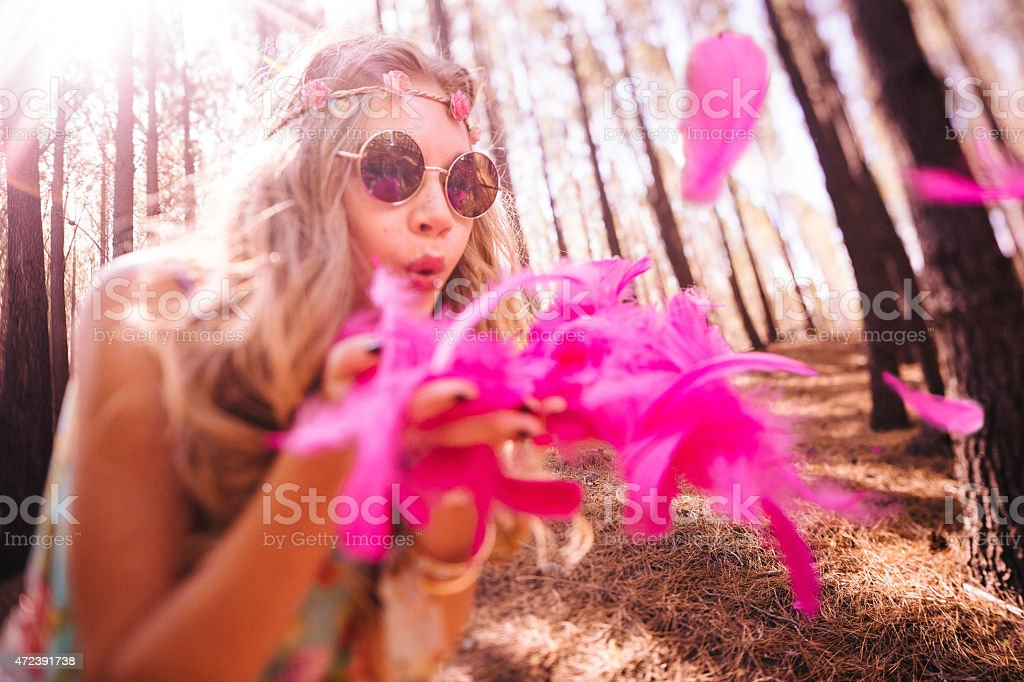 Boho girl blowing brightly coloured pink feathers stock photo