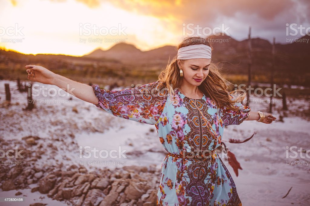 Boho girl dancing in floral dress on a summer evening stock photo