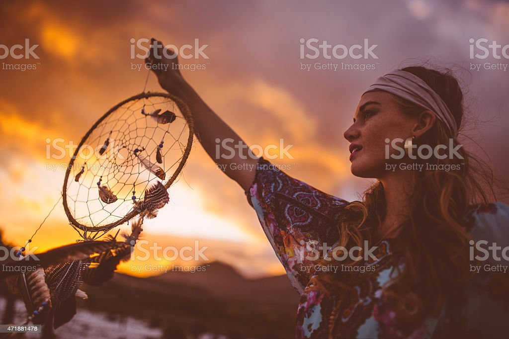 Boho girl holding up a dream catcher on summer evening stock photo