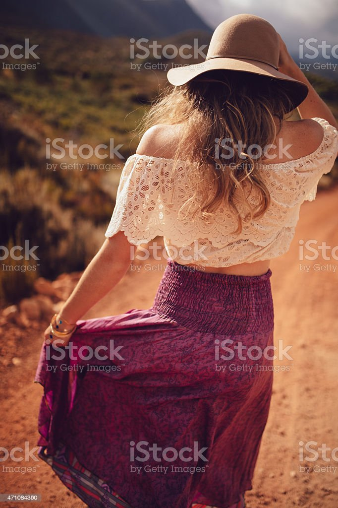 Boho girl in purple skirt walking down a dirt road stock photo